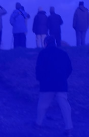 a photo of a man walking towards a group of people with their back to him