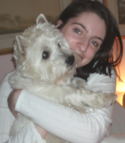 a photo of Emily holding Bella, her dog, a white westie